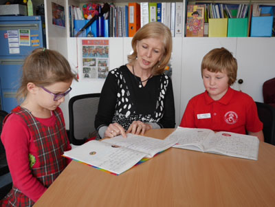 Principal, Anne Simpson, with children and their writing work.